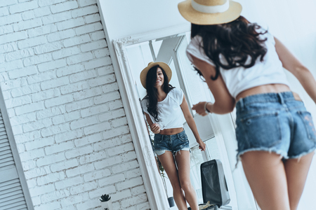 Ready for summer adventures. Rear view of attractive young woman trying on her sun hat and smiling while looking in the mirror at home Banco de Imagens