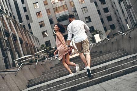 Carefree day together. Full length rear view of playful young couple holding hands and smiling while running up the stairs outdoors