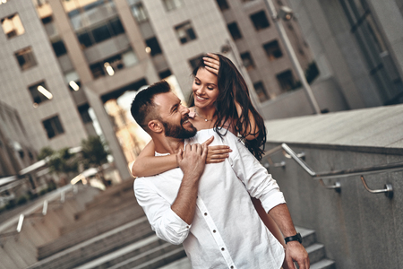 Making each other happy. Attractive young woman embracing her handsome boyfriend while spending time together in the city Archivio Fotografico