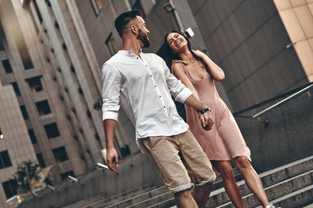 Couple on the go. Beautiful young couple holding hands and smiling while walking outdoors photo