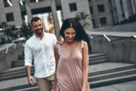 Verrast door haar schoonheid. Mooie jonge vrouw lachend terwijl ze door de stadsstraat met haar vriendje loopt Stockfoto - 82663632