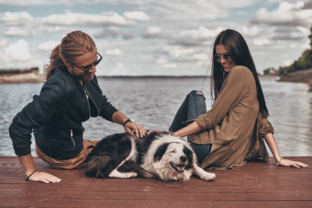 Couple with dog. Beautiful young couple playing with dog while sitting near the lake outdoors Banque d'images