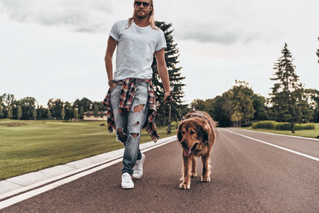 Moving forward together. Full length of handsome young man walking with his dog while spending time outdoors
