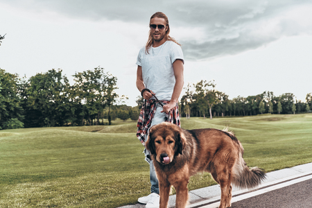 Great companion. Full length of handsome young man standing with his dog while spending time outdoors