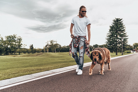 Always together. Full length of handsome young man walking with his dog while spending time outdoors