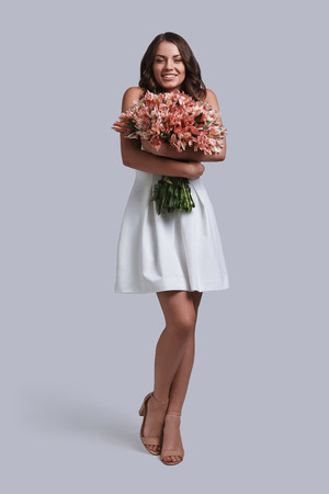 Who is her secret admirer? Full length of attractive young woman holding her flower bouquet and smiling while standing against grey background Banque d'images
