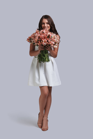 She deserves beautiful flowers. Full length of attractive young woman holding her flower bouquet while standing against grey background