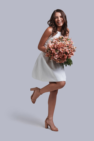 Pretty as a flower. Full length of attractive young woman holding flower bouquet and smiling while posing against grey background Reklamní fotografie