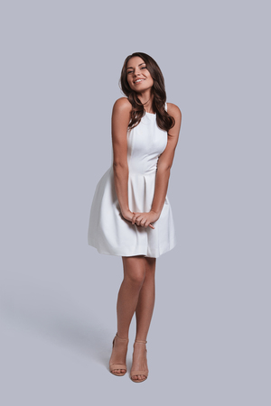 Perfect female. Full length of attractive young woman in white dress looking at camera and smiling while posing against grey background Banque d'images