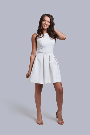 Gorgeous beauty. Full length of attractive young woman in white dress looking at camera and smiling while standing against grey background