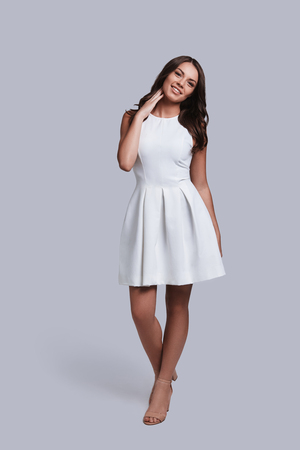 Naturally beautiful. Full length of attractive young woman in white dress looking at camera and smiling while standing against grey background