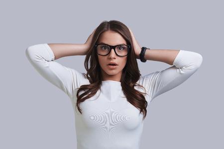 Auf keinen Fall! Entsetzte junge Frau, die Gesicht bei der Stellung gegen grauen Hintergrund bildet Standard-Bild - 83650703