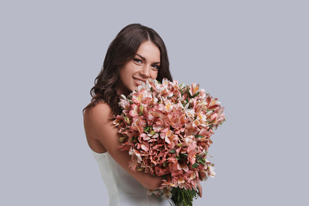 Lovely flowers. Attractive young woman with flower bouquet looking at camera and smiling while standing against grey background