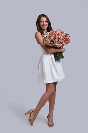 Her favorite flowers. Full length of attractive young woman holding her flower bouquet while standing against grey background