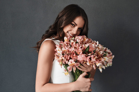 Flowers are gifts from the heart. Attractive young woman with flower bouquet looking at camera and smiling while standing against grey background