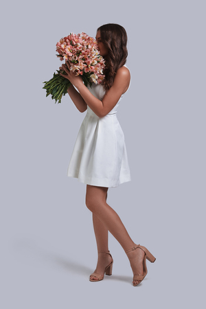 Beauty with flowers. Full length of attractive young woman smelling her flower bouquet while standing against grey background