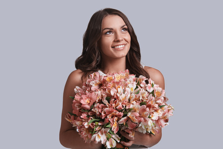 Charming girl. Attractive young woman with flower bouquet looking away and smiling while standing against grey background