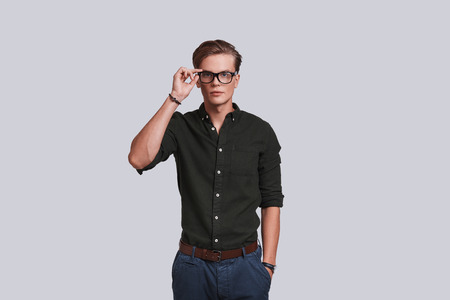 Taking everything seriously. Good looking young man adjusting his eyewear and keeping hand in pocket while standing against grey background