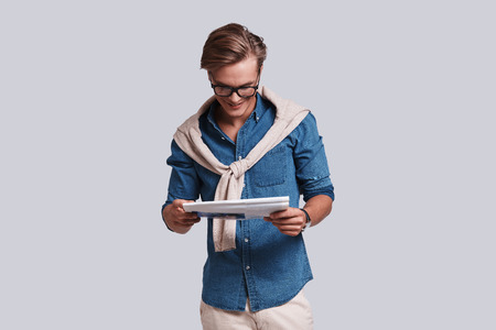 What is happening in the world?  Handsome young man reading newspaper and smiling while standing against grey background