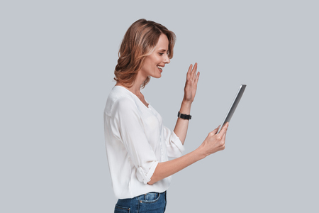Nice to see you! Side view of beautiful young woman looking at digital table and waving with a smile on her face while standing against grey background Imagens - 86526654
