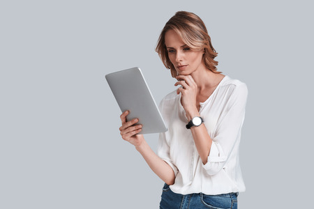 Interesting.... Thoughtful young woman looking at digital table and keeping hand on chin while standing against grey background