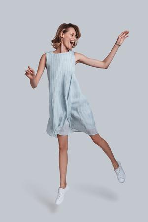 動きの美。遊び心のある若い女性のジェスチャの全長は、灰色の背景に向かってジャンプしながら、口を開いたままにします 写真素材 - 86526667