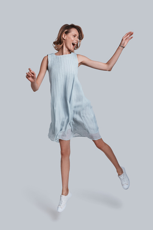 Beauty in motion. Full length of playful young woman gesturing and keeping mouth open while jumping against grey background Stock Photo