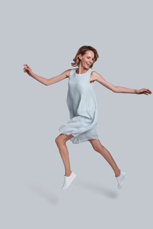Beauty in the mid-air. Full length of playful young woman gesturing and keeping mouth open while jumping against grey background