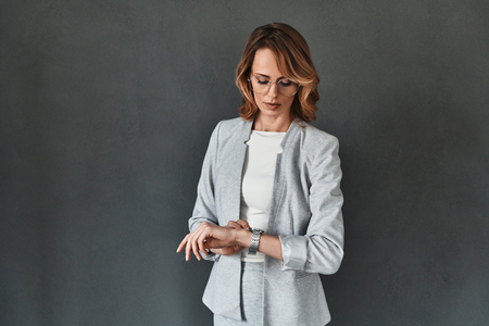 Time to do business. Thoughtful young woman in smart casual wear checking the time while standing against grey background Stock Photo