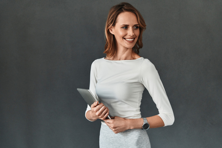Young perfectionist. Beautiful young woman in smart casual wear holding digital tablet and smiling while standing against grey background