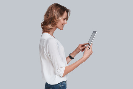 Using modern technologies. Attractive young woman holding digital tablet and looking at it while standing against grey background
