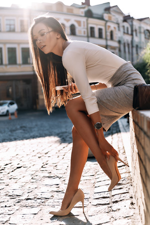 Her shoe gives her trouble. Attractive young woman adjusting her shoe and keeping eyes closed while sitting outdoors Imagens