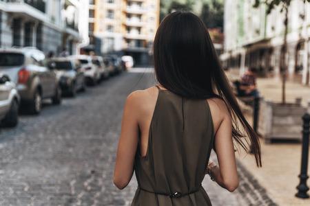 Tijd om weg te komen van alles ... Achteraanzicht van jonge vrouw lopend onderaan de straat terwijl tijd buitenshuis doorbrengen Stockfoto