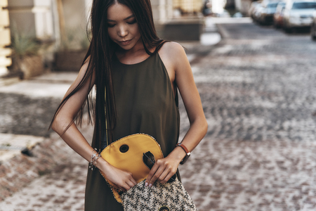 Searching for something. Attractive young woman keeping purse open while standing outdoors