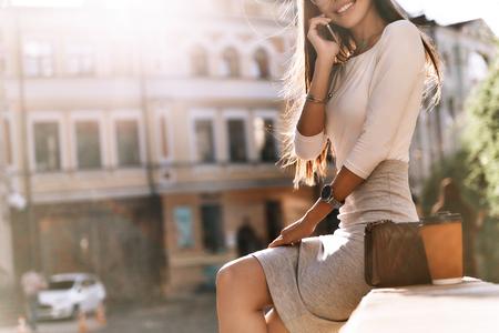 私は完全にそれを行うことができます! 屋外で座りながらスマート フォンで話している魅力的な若い女性をクローズ アップ