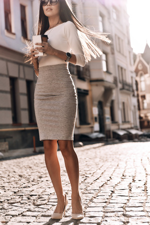 本当の美しさ。屋外を歩きながら彼女のスマート フォンと使い捨てカップを保持している魅力的な若い女性