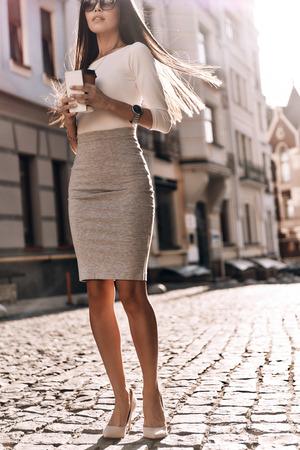 진짜 아름다움. 야외에서 산책하는 동안 그녀의 스마트 전화 및 일회용 컵을 들고 매력적인 젊은 여자