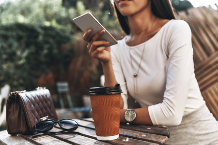 Receiving good feedbacks.  Close-up of young woman holding a smart phone while sitting in restaurant outdoors Stock Photo
