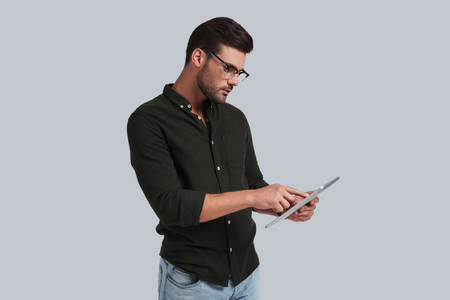 Examining his digital tablet. Serious young man in eyeglasses working on his digital tablet while standing against grey background