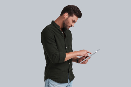 Putting ideas into something real. Serious young man working on his digital tablet while standing against grey background Stock fotó