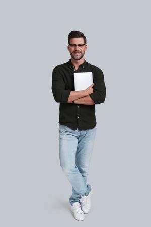 単なるデバイス。デジタル タブレットの彼を押しながら灰色の背景に対して立っている笑顔の眼鏡で良い探している若い男の完全な長さ
