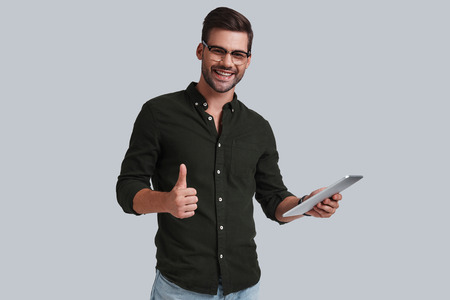 Receiving good feedbacks. Good looking young man in eyeglasses holding his digital tablet and gesturing while standing against grey background