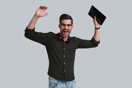 Happy to end the project! Good looking young man in eyeglasses holding his digital tablet and gesturing while standing against grey background