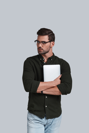 Always online. Good looking young man in eyeglasses holding his digital tablet and looking away while standing against grey background
