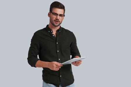 How may I help you? Good looking young man in eyeglasses holding his digital tablet and looking at camera while standing against grey background