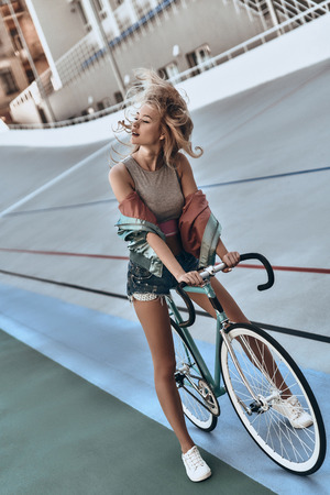 Nice day for a ride. Full length of attractive young woman in casual clothing standing with her bicycle outdoors