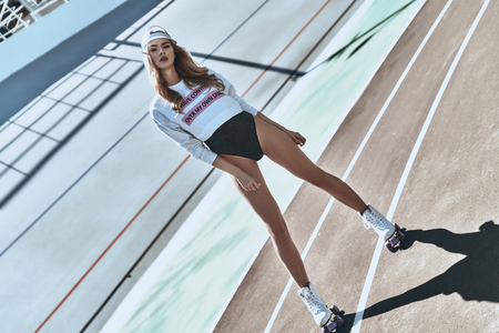 Seductive young female. Full length of attractive young and trendy woman in roller skates standing on stadium outdoors
