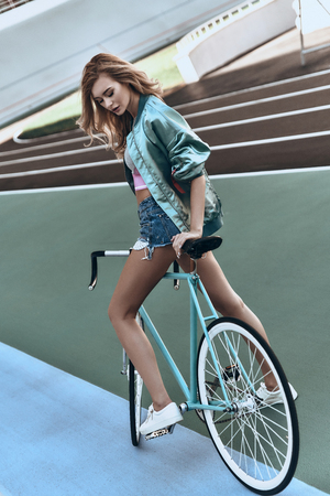 Ready to go. Full length of attractive young woman in casual standing with her bicycle outdoors Banco de Imagens - 88224323