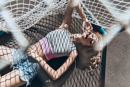 Absolutely beautiful. Top view of attractive young woman in casual wear touching her face with hand while lying down outdoors 版權商用圖片