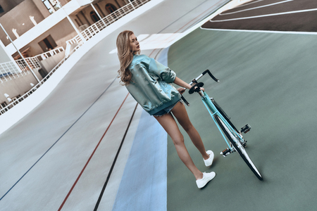 Time for some rest. Full length rear view of attractive young woman in casual clothing looking away while walking with her bicycle outdoors